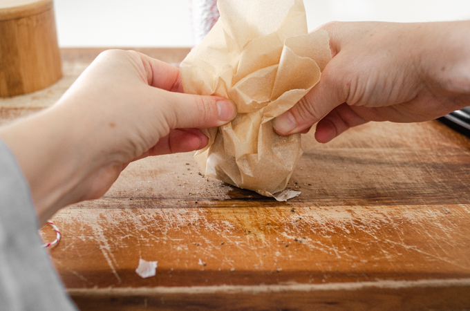 Gathering the sides of the parchment paper up.