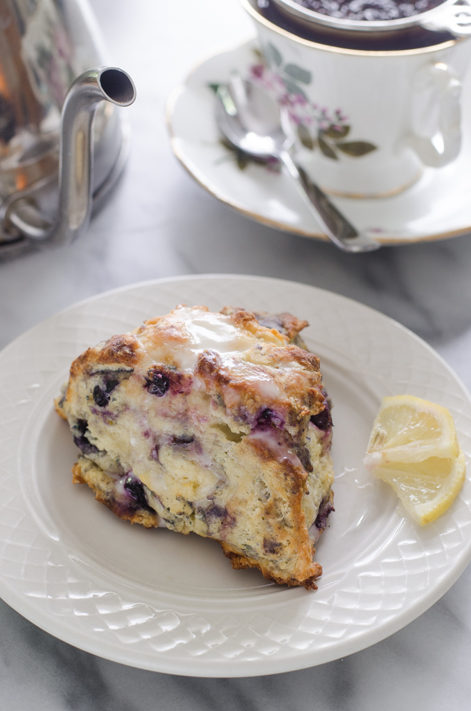 Blueberry scones on a dessert plate with small slices of lemon off to the side and a cup of tea and a tea pot in the background.