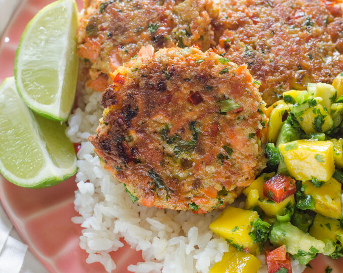 A pink plate with rice, salmon cakes, and mango salsa with lime wedges.
