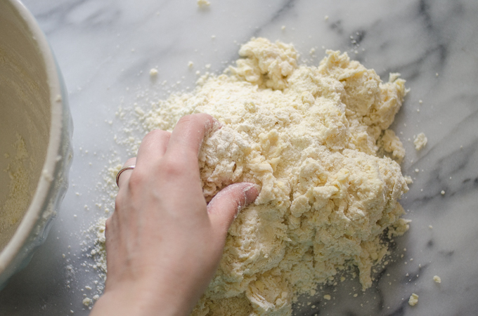 Dough dumped out on a marble work surface.