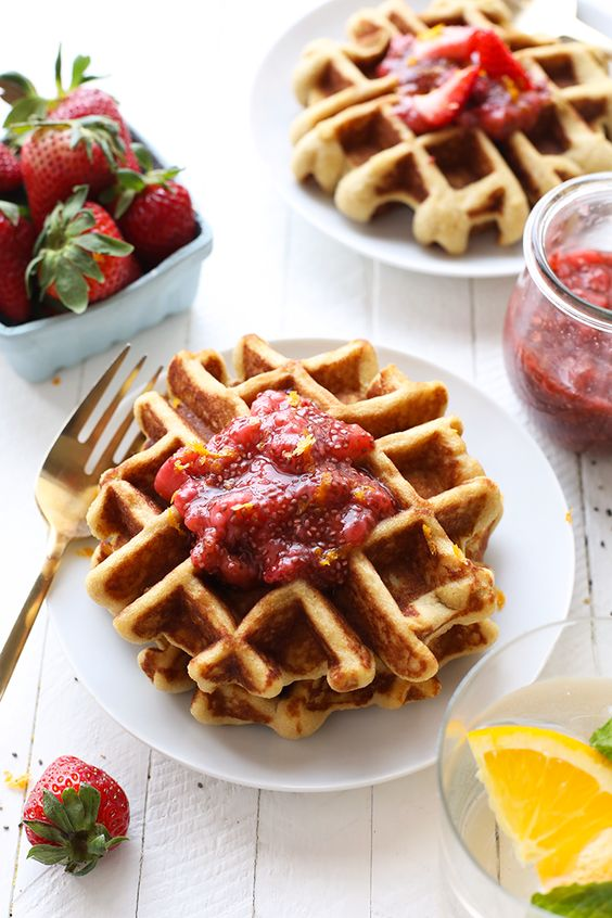 Waffles on plates with jam on top.