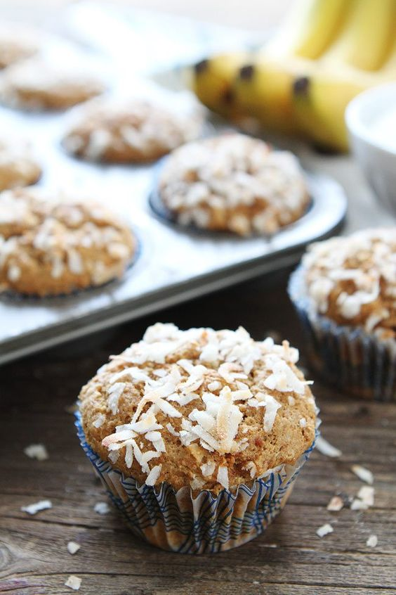 Banana coconut muffin sitting next to a muffin tin.