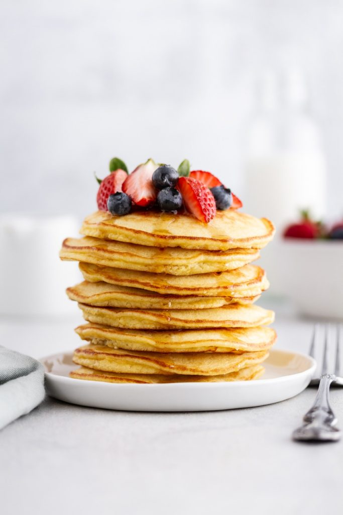 Stack of coconut flour pancakes with fresh berries on top.