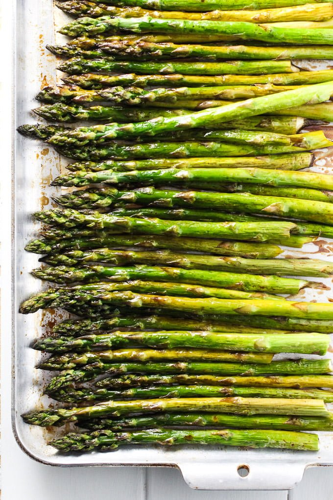 From above view of roasted asparagus on a baking tray.