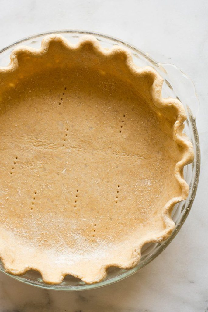 From above view of an unbaked pie crust, crimped, in a pie pan.
