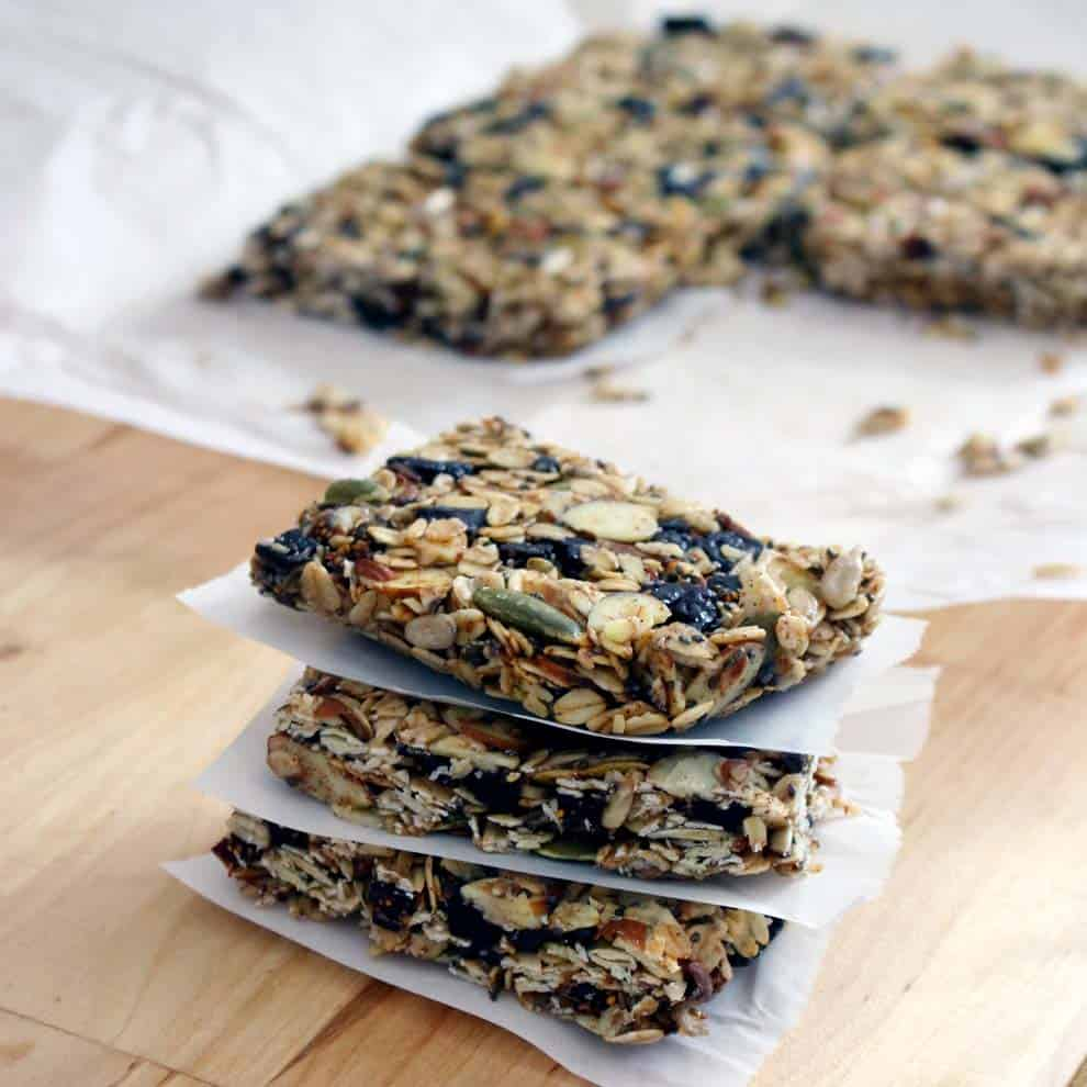 Stack of granola bars with pieces of parchment paper between them.