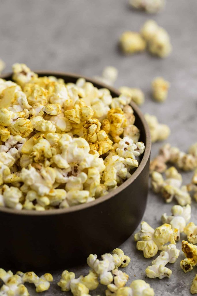 Bowl of coconut curry popcorn with pieces scattered around.