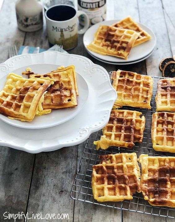 Eggnog waffles on a cooling rack and on plates with mugs in the background.