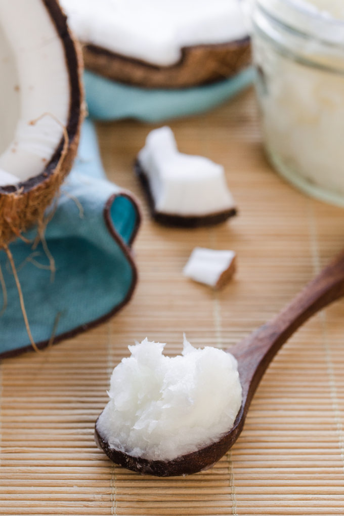 A scoop of coconut oil on a bamboo mat with fresh coconut pieces in the background.