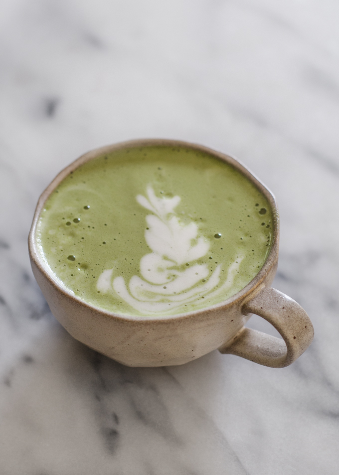 Matcha latte in a stoneware mug with latte art.
