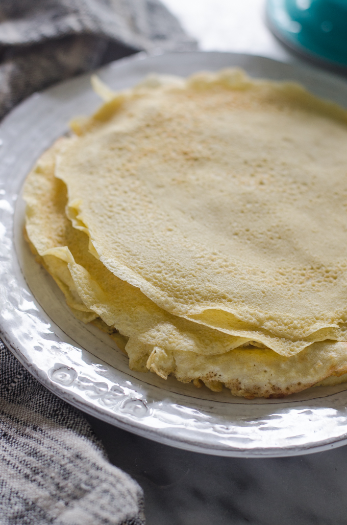 Stack of crepes on a plate with a linen napkin next to it.