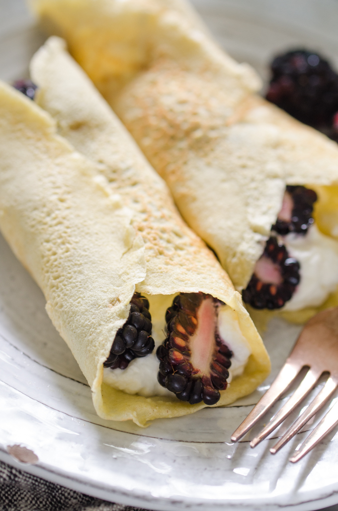Close up shot of KETO crepes filled with whipped cream and blackberries.