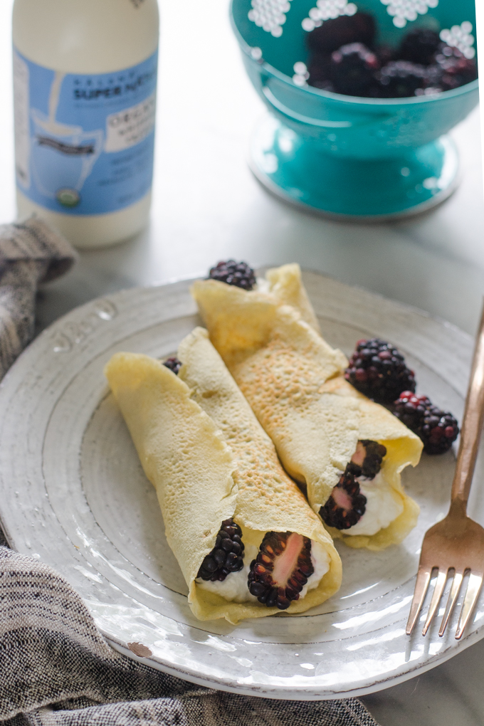 KETO crepes filled with whipped cream and blackberries on a plate on a marble surface.