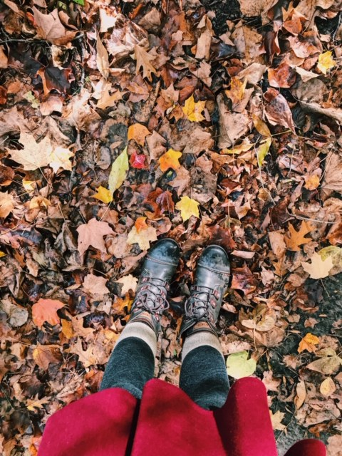 Photo of fallen leaves with feet in the picture.