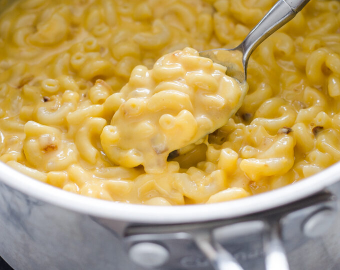 A spoonful of butternut squash mac and cheese held over the pot.