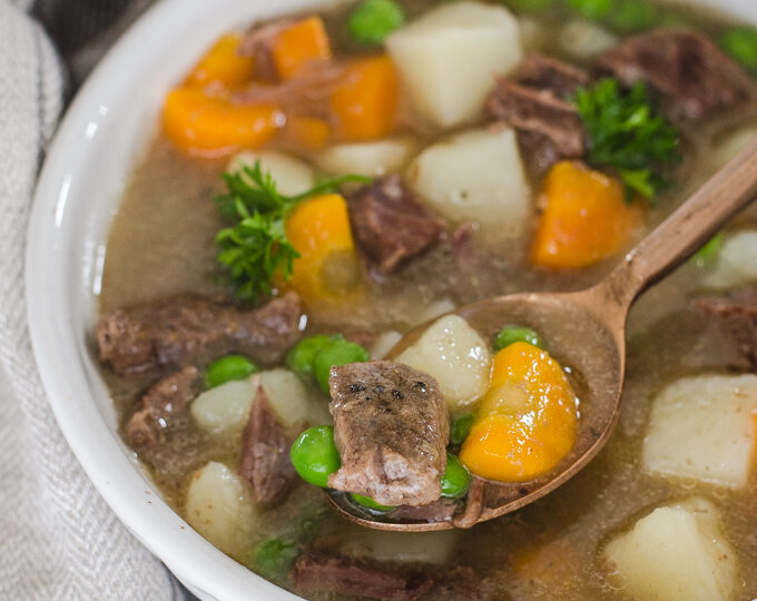 A bowl of Instant Pot Beef Stew with a napkin off to the side and a spoon.