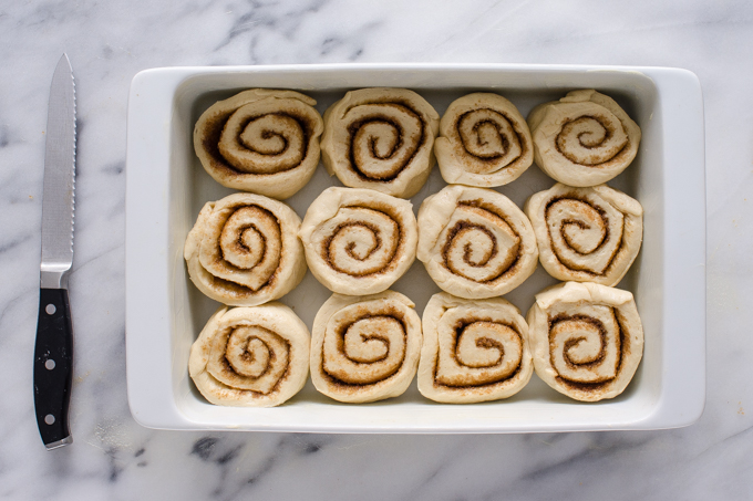 The eggnog cinnamon rolls in a white baking dish.