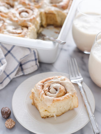 An individual eggnog cinnamon roll on a plate with the pan in the background.
