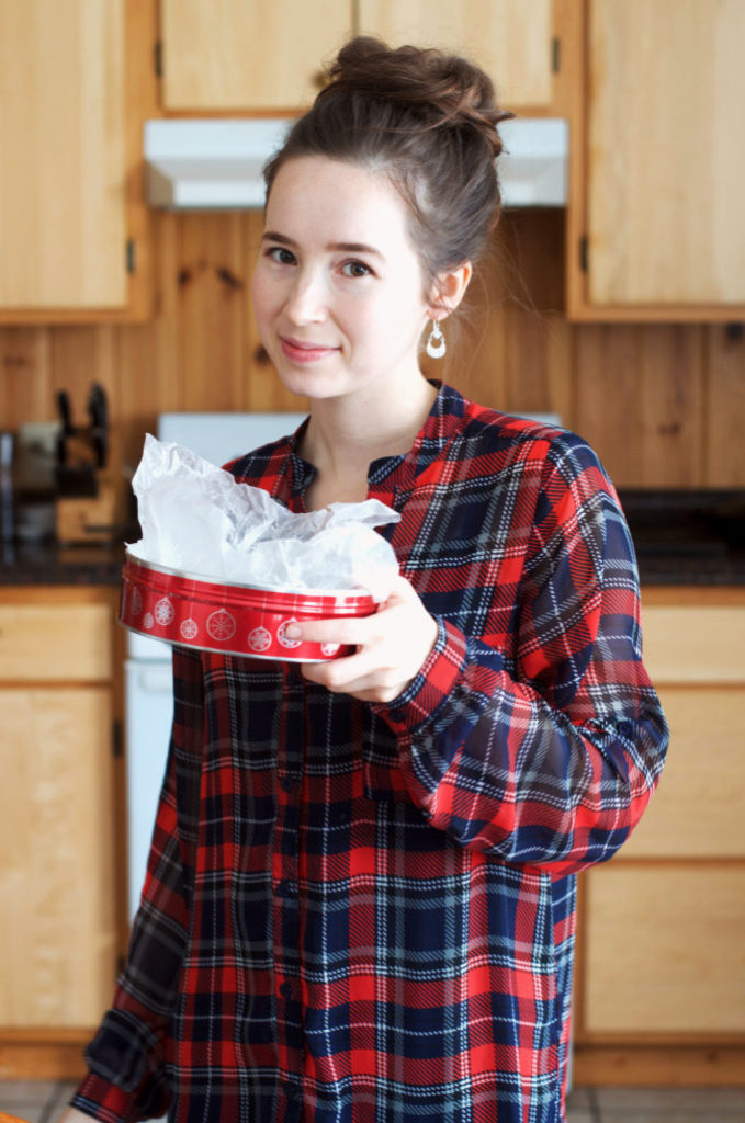 Woman in a plaid shirt holding a Christmas tin.