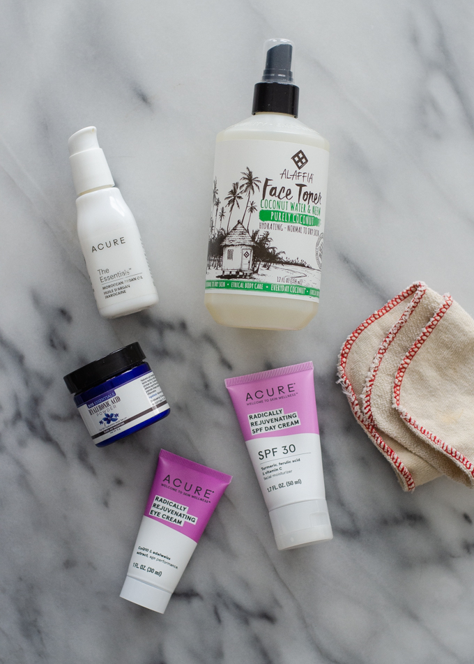 Products for a 5 step winter skin care routine for dry skin laid out on a marble surface.