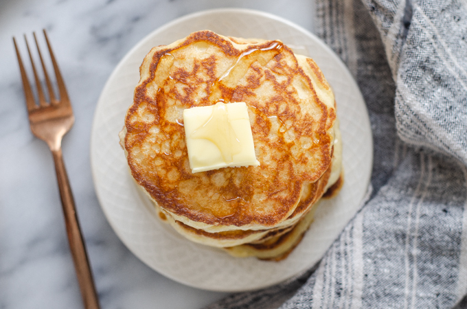 A stack of sourdough pancakes with a pat of butter and drizzle of maple syrup on top.