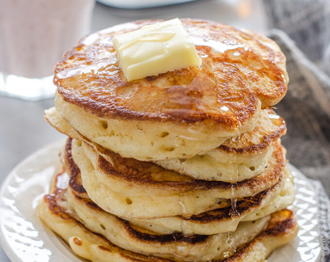 A stack of sourdough pancakes with a pat of butter and maple syrup dripping off the sides.