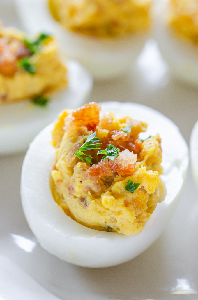 Close up shot of deviled eggs with bacon and parsley.