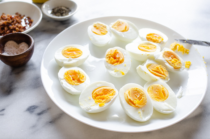 Hard boiled eggs sliced in half on a plate.
