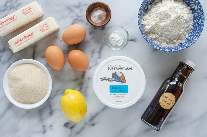 All of the ingredients for a sour cream pound cake loaf laid out on a marble surface.