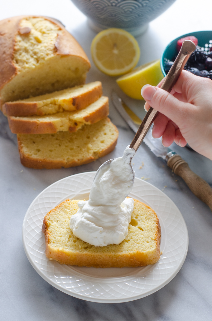 Topping the slice with whipped cream.