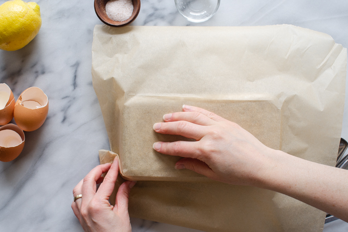 Folding parchment paper around the outside of a pan to make it fit better.