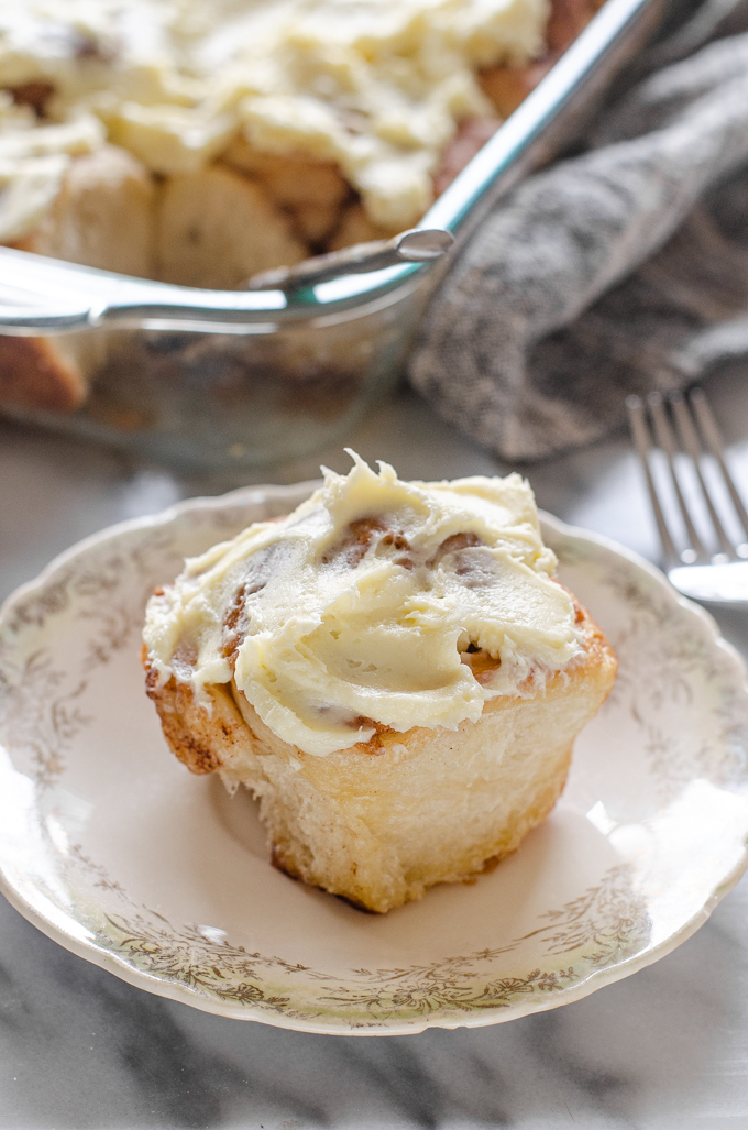 A sourdough cinnamon roll with cream cheese icing on a small plate.