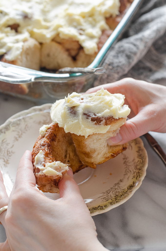 Pulling apart a sourdough cinnamon roll with cream cheese icing on top.