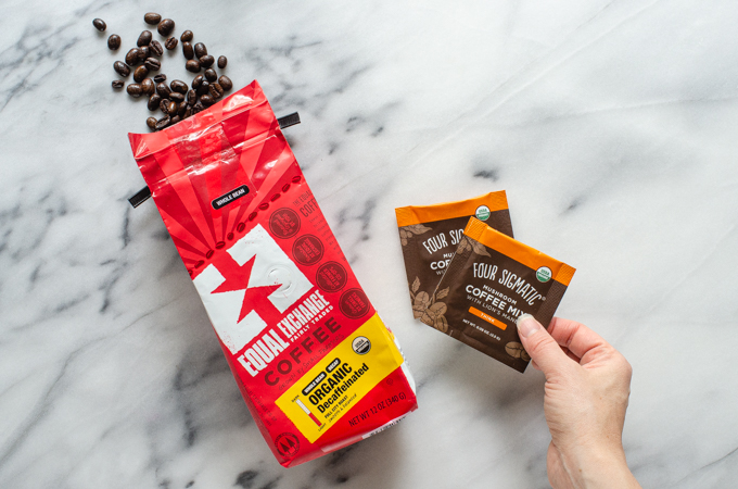 Equal Exchange and Foursigmatic coffee on a marble surface.