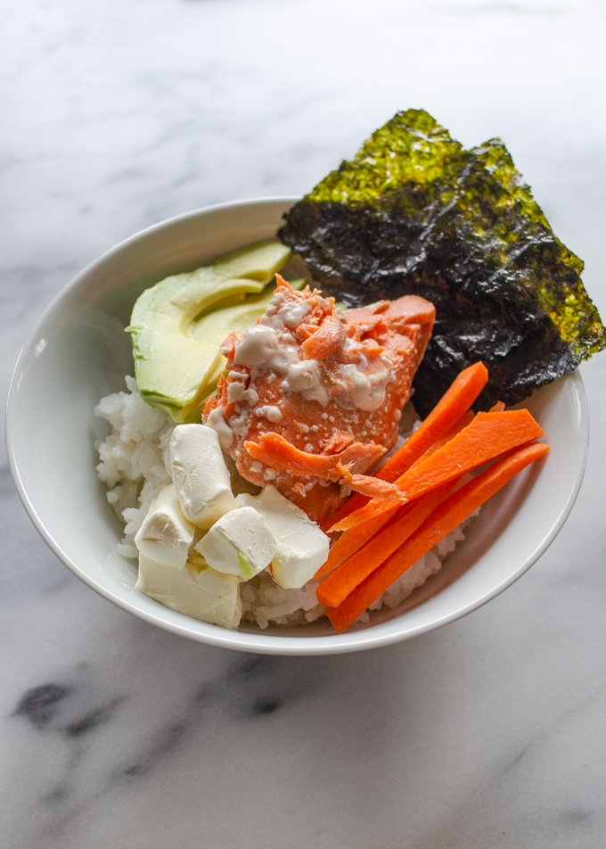 A bowl of sushi rice topped with avocado, seaweed snacks, carrots, cream cheese, and salmon.