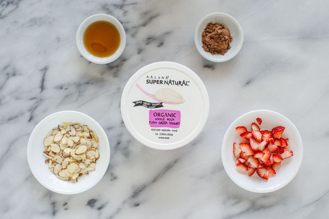 Ingredients for a chocolate strawberry yogurt bowl laid out on a marble surface.