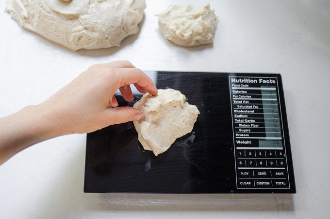 Placing a piece of dough on a scale to weigh it.