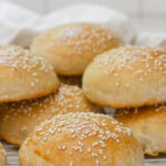 Sourdough hamburger buns on a cooling rack.