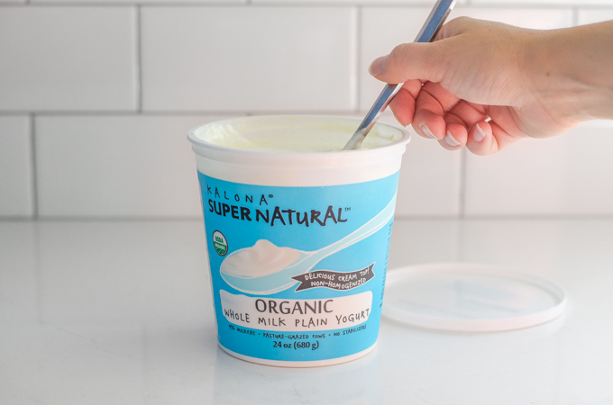 Mixing Kalona SuperNatural yogurt with a spoon.
