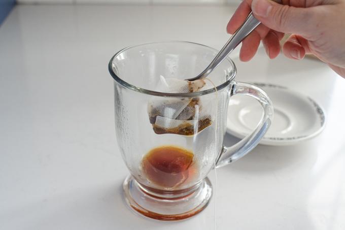 Squeezing out the chai tea bag into the mug.