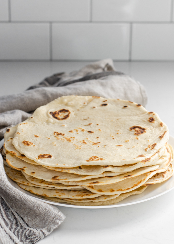Sourdough tortillas stacked on a plate with a tea towel around them.