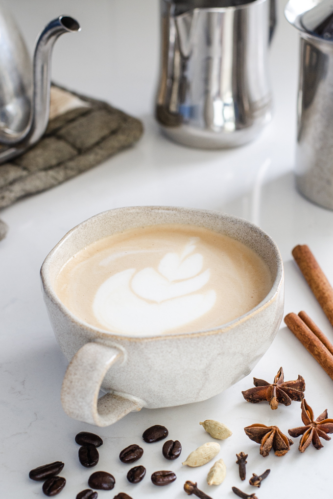 A mug of dirty chai latte with spices around it.