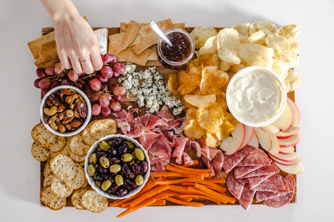 Adding the grapes, carrots, and apples to the snack board.
