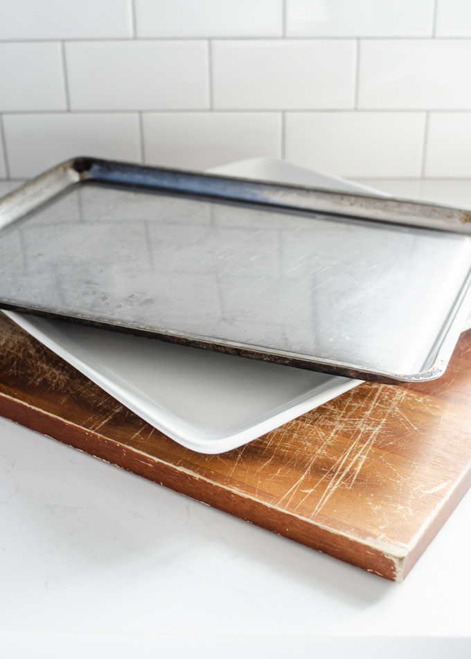 A cutting board, large plate, and cookie sheet stacked on top of each other.