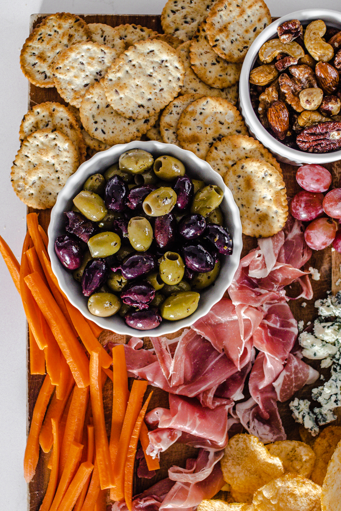 Olives, crackers, roasted nuts, grapes, prosciutto, blue cheese, chips, and carrots.