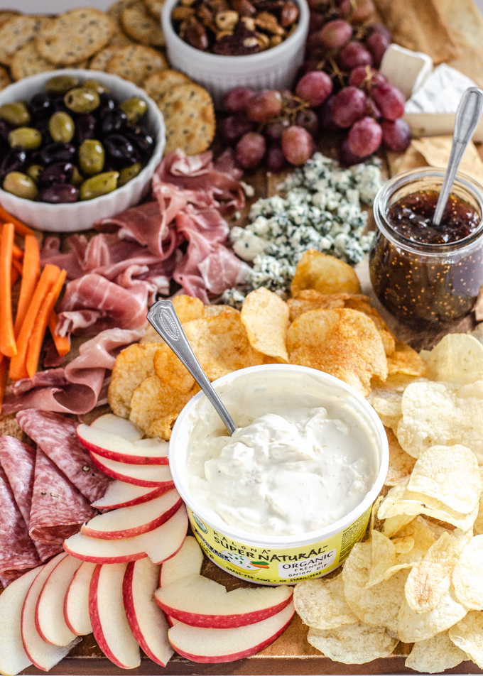 A snack board with nuts, crackers, grapes, brie cheese, fig spread, olives, blue cheese, prosciutto, carrots, chips, apples, salami, and Kalona SuperNatural French onion dip.