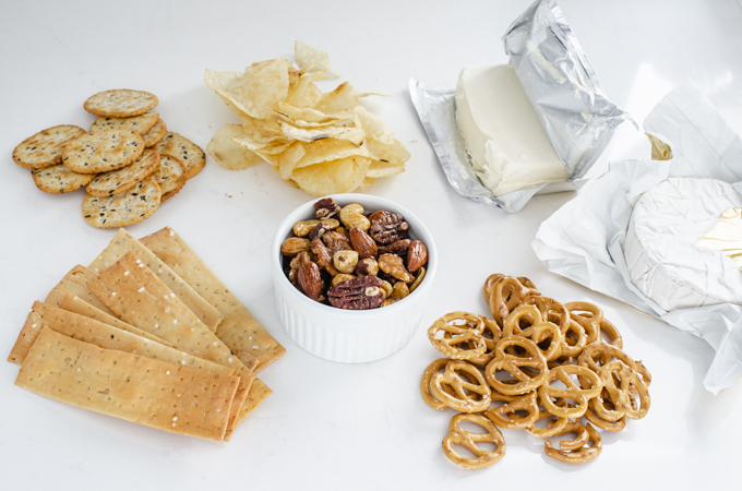 Crackers, chips, roasted nuts, pretzels, cream cheese, and brie cheese laid out on a counter.