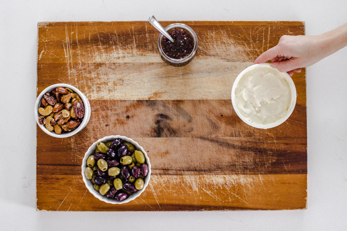 Arranging containers of snacks on a wooden cutting board.