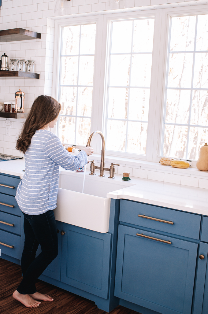 Blue transitional cabinets with white quartz countertops and a white apron front sink in front of window.