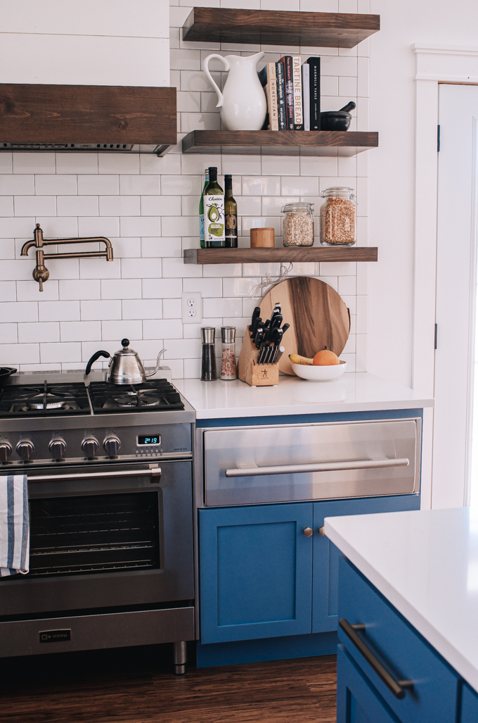 Open shelving in a transitional kitchen with subway tile backsplash up to the ceiling.